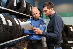 Customer and salesman at car service or auto store. Business, maintenance and people concept - male customer choosing wheel discs and salesman with clipboard at stock images