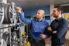 Customer and salesman at car service or auto store stock photo