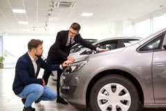 Customer and salesman choose a car in the showroom.  stock photo