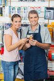 Customer And Salesman Holding Flashlight In Store Stock Images