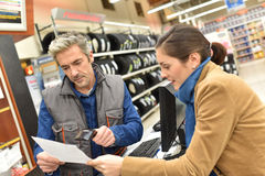Customer and salesman with invoice at car store stock photography
