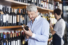 Customer And Salesman Looking At Wine Bottles Stock Photos