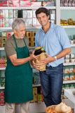 Customer With Salesman Putting Vegetable In Paper Stock Photo