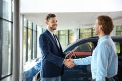 Customer and salesman shaking hands. In car dealership royalty free stock photos