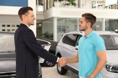 Customer and salesman shaking hands. In car salon stock image