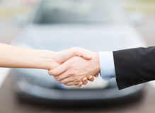 Customer and salesman shaking hands. Transportation, business, shopping and ownership concept - customer and salesman shaking hands outside royalty free stock image