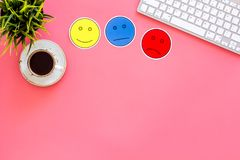 Customer satisfaction concept. Emoji smile, neutral, sad on work desk on pink background top view copy space royalty free stock photos