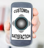 Customer satisfaction concept on a smartphone. Hand holding a smartphone with customer satisfaction concept Stock Photo