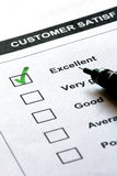 Customer satisfaction service. Form  with check boxes and a pen, The first of them is checked in green. The focus is on the checked box Royalty Free Stock Image