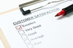 Customer satisfaction survey. Form on clipboard with red pen royalty free stock photo