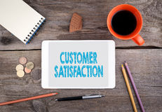 Customer Satisfaction. Tablet device on a wooden table Royalty Free Stock Photo