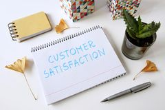 Customer satisfaction written in a notebook. On white table stock photos