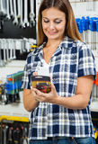 Customer Scanning Product's Barcode On Mobilephone. Mid adult female customer scanning product's barcode on mobilephone in hardware store Stock Photo