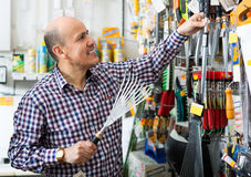Customer selecting garden rakes. Male retiree selecting garden rakes in building store Stock Image