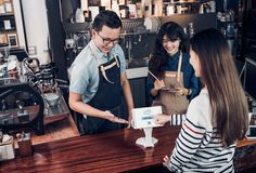 Customer self service order drink menu with tablet screen and pa. Y bill online at cafe counter bar,seller coffee shop accept payment by mobile.digital lifestyle Stock Photo
