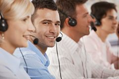 Customer service. Young customer service operator wearing headset, looking at camera, smiling royalty free stock image