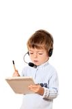 Customer Service. A three year old boy wearing a customer service headset taking notes Royalty Free Stock Photography