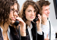 Customer service. Young customer service operator team working at office, holding phone, calling, giving helpdesk support Royalty Free Stock Photography