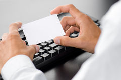 Customer service. Hand with white card in front of a computer keyboard Stock Photography