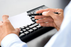 Customer service. Hand with white card in front of a computer keyboard Stock Images