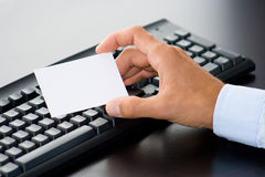 Customer service. Hand with white card in front of a computer keyboard Stock Photos