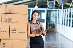 Customer Service in Asian logistics warehouse. Young Asian woman in a suit with headset in a Indonesian logistics warehouse, she is from the Customer Service Royalty Free Stock Image