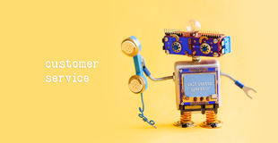 Customer service call center operator concept. Friendly robot assistant with retro styled phone on yellow background. royalty free stock images