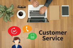 THE CUSTOMER SERVICE and Customer Service Call Center Agent Care. (Target Market Support Assistance) Hipster wooden desktop with laptop, office accessories Royalty Free Stock Photography