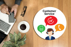 THE CUSTOMER SERVICE and Customer Service Call Center Agent Care. (Target Market Support Assistance) Hipster wooden desktop with laptop, office accessories Royalty Free Stock Images