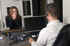 Customer at a service desk. Customer getting some information at a service desk Royalty Free Stock Images