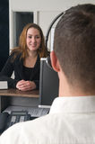 Customer at a service desk. Customer getting some information at a service desk Royalty Free Stock Photos