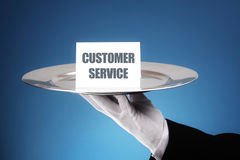 Customer service excellence. Butler or waiter holding a card reading customer service on a silver platter concept for first class or excellence royalty free stock photos
