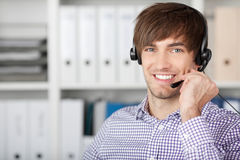 Customer Service Executive Using Headset In Office. Portrait of handsome customer service executive using headset in office Royalty Free Stock Photos