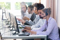 Customer Service Executives Working In Call Center. Young Customer Service Executives Using Earphones Working In Call Center royalty free stock photo