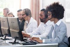 Customer Service Executives Working In Call Center. Young Customer Service Executives Using Earphones Working In Call Center royalty free stock photos