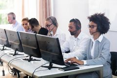 Customer Service Executives Working In Call Center. Young Customer Service Executives Using Earphones Working In Call Center stock photography