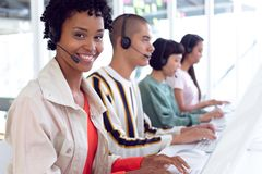 Customer service executives working on computer at desk. Portait of African-american customer service executives working on computer at desk in office stock photography