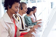 Customer service executives working on computer at desk. Side view of diverse customer service executives working on computer at desk in office royalty free stock image