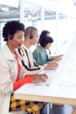 Customer service executives working on computer at desk. Side view of diverse customer service executives working on computer at desk in office royalty free stock photography