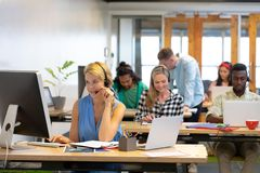 Customer service executives working at desk in a modern office. Front view of diverse customer service executives working at desk in a modern office stock photo
