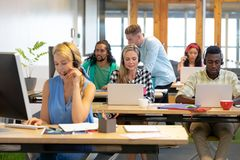 Customer service executives working at desk in a modern office. Front view of diverse customer service executives working at desk in a modern office stock photography