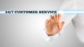 24/7 customer service. Male hand activating a 24/7 customer service button on virtual screen Stock Image