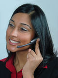 Customer Service Operator. Asian Girl talking into a telephone headset Royalty Free Stock Images