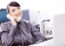 Customer service operator. Happy young female customer service operator talking on landline phone, sitting in front of computer screens, smiling Stock Image