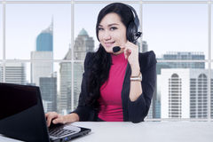 Customer service operator smiling at camera. Portrait of beautiful customer service operator working in the office with laptop and headphones Stock Photos