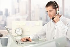 Customer service operator working in bright office. Male customer service operator working in bright office stock image