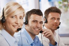 Customer service operators. Happy young customer service operators talking on headset, eye contact, smiling Stock Photo