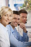 Customer service operators. Happy young customer service operators talking on headset, eye contact, smiling Stock Photography
