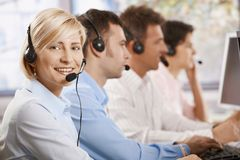 Customer service operators. Happy female customer service operator recieving calls on headset, looking at camera, smiling Royalty Free Stock Photos