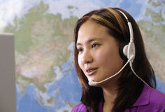 Customer service rep. Woman wearing headset with map of world Royalty Free Stock Image